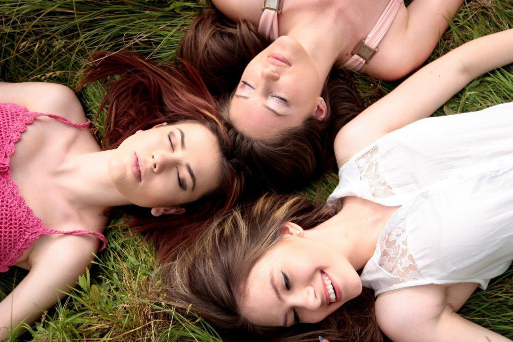 女性が3人で笑顔で寝そべってる画像