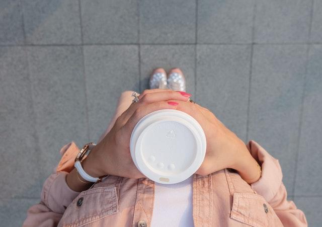 コーヒーカップを持って立ち尽くす女性